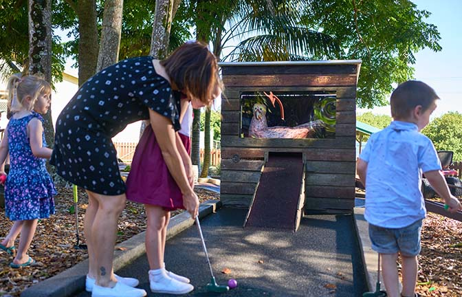 A child prepares to putt the ball at mini golf