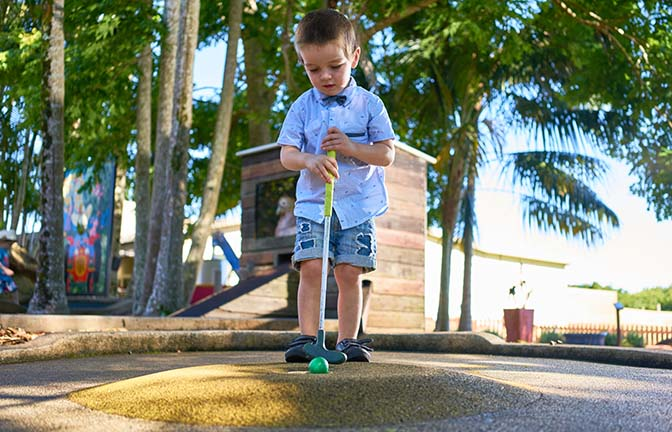 A child putts the ball into a mini golf hole