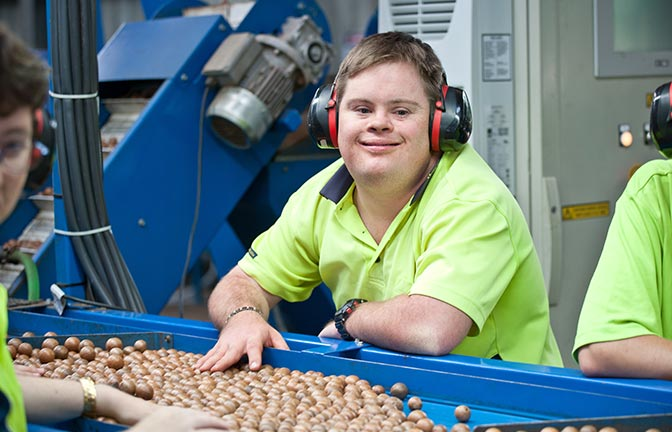 A smiling worker at a macadamia grading machine