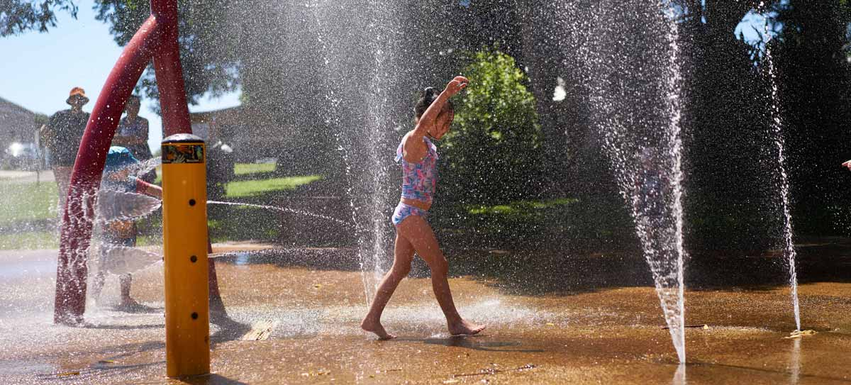 A child plays under a fountain at a water park
