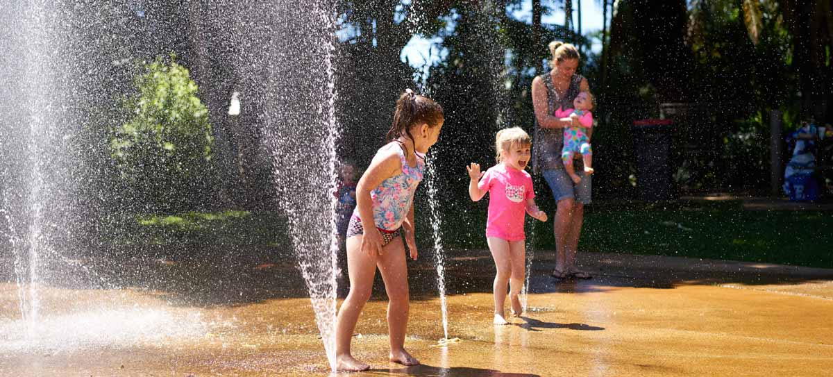 Children play under a water jet at a water park