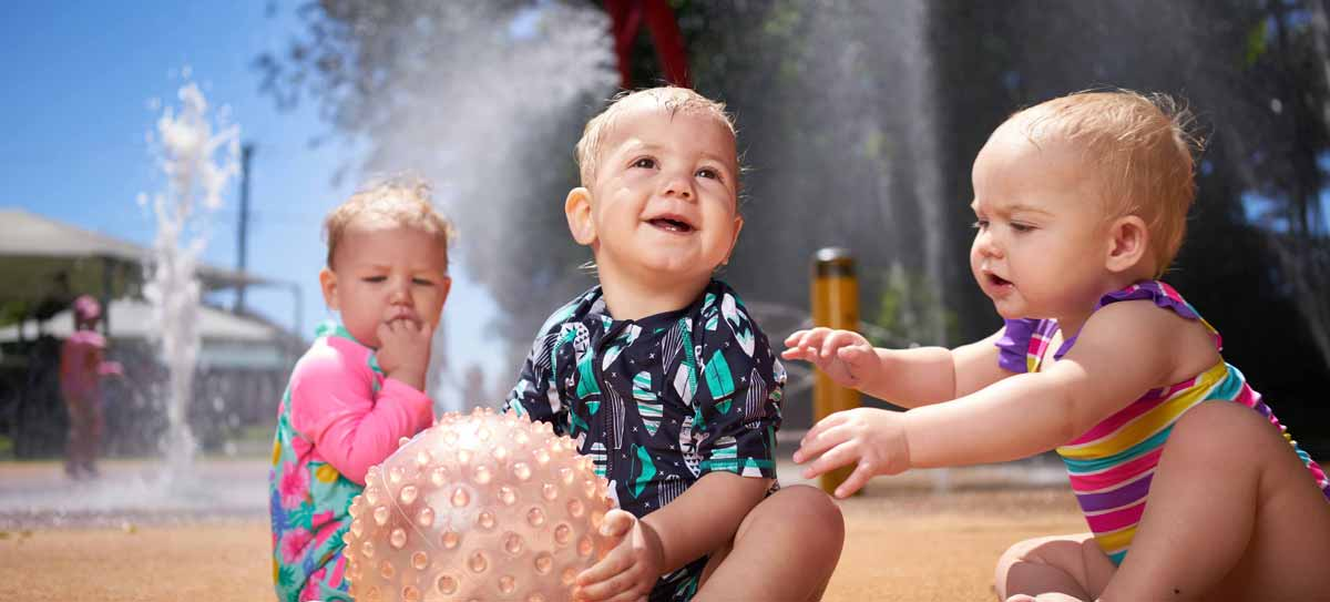 Young children play with a ball at a water park