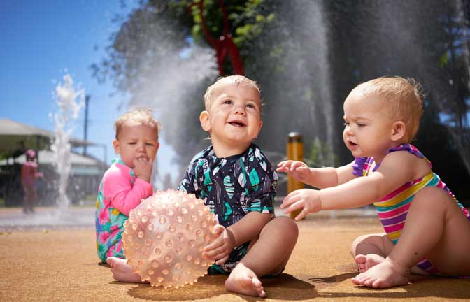 Young children play with a ball in a water park