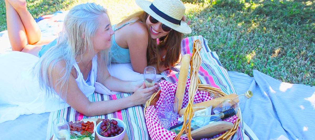 Friends smiling on a picnic rug with food and drink