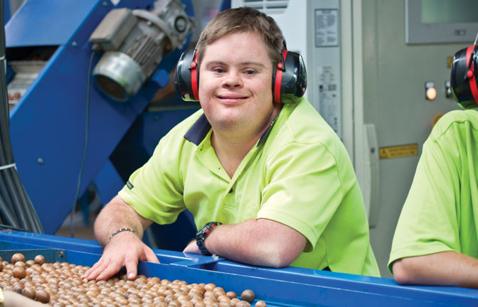 A smiling worker stands at a grading machine in a packing shed