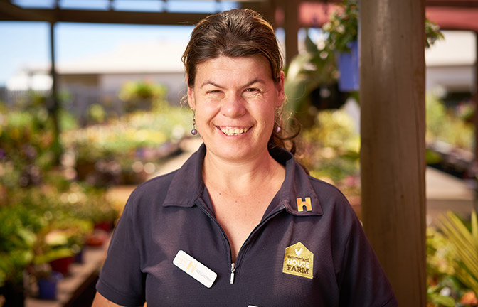 A Summerland House Farm employee with a big smile on her face. She is wearing her uniform.